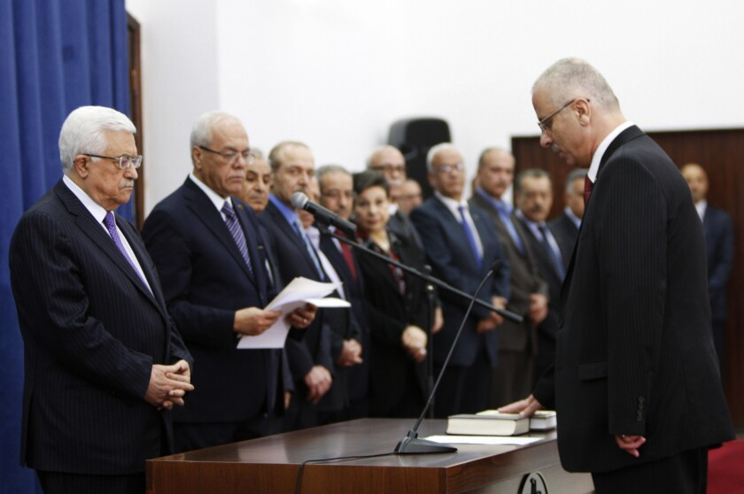 Palestinian Prime Minister Rami Hamdallah, right, takes the oath of office in front of President Mahmoud Abbas, left, and other officials in the West Bank city of Ramallah.