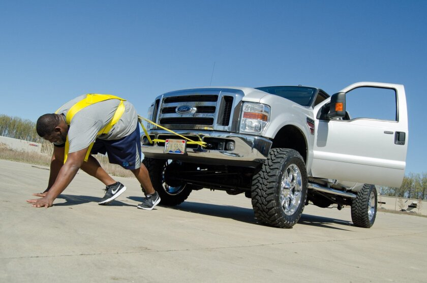 The Chargers' Tyronne Green pulls a Ford F-250 truck as part of his offseason conditioning program at the O-Line Academy in Avon, Ohio. Al Fuchs