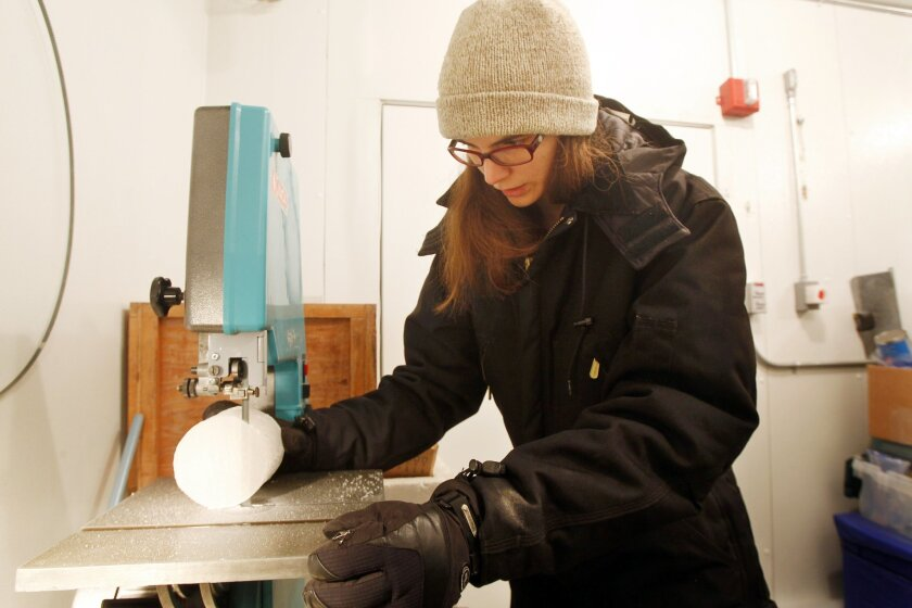 Anais Orsi, a researcher at the Scripps Institution of Oceanography, cuts a sample of an Antarctic ice core
