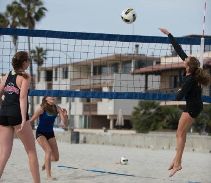 La Jolla High School's Bridget Odmark spikes against Scripps Ranch as teammate Riley Young (far left) looks on. Ed Piper