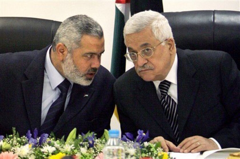 FILE- In this March 18, 2007 file photo, Palestinian Authority President Mahmoud Abbas, right, and Palestinian Prime Minister Ismail Haniyeh of Hamas, left, speak as they head the first cabinet meeting of the new coalition government at Abbas' office, in Gaza City. After four years of turbulent rule in the Gaza Strip, the Islamic militant group Hamas is weighing a new strategy of not directly participating in future governments even if it wins elections, an approach aimed at avoiding isolation by the world community and allowing for continued economic aid. (AP Photo/Khalil Hamra, File)