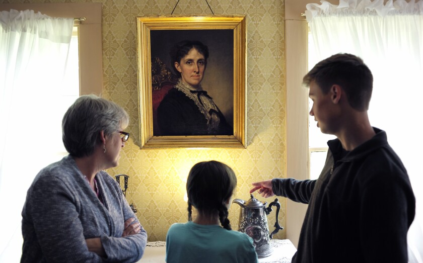 Museum visitors view a portrait of author Louisa May Alcott by artist George Healy at Orchard House in Concord, Mass.