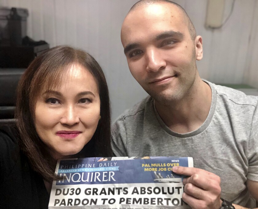 In this photo provided by Atty. Rowena Garcia-Flores, U.S. Marine Lance Cpl. Joseph Scott Pemberton, right, poses for a selfie while showing the headlines of a newspaper beside his lawyer Rowena Garcia-Flores on Tuesday Sept. 8, 2020 in Camp Aguinaldo, Quezon city, Philippines. The Philippine president recently pardoned Pemberton in a surprise move that will free him from imprisonment in the 2014 killing of a transgender Filipino woman that sparked anger in the former American colony. (Atty. Rowena Garcia-Flores via AP)