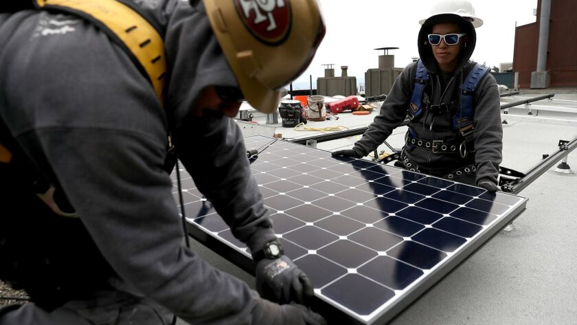 Workers install a solar system on the roof of a home in San Francisco on May 9, 2018.
