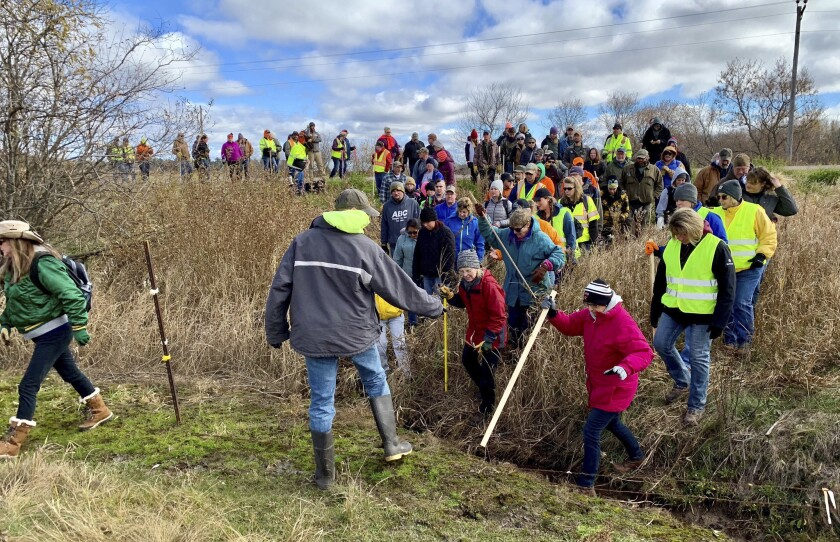 Volunteers cross a creek and barbed wire near Barron, Wis., on Tuesday. About 2,000 people looked for clues in connection with the disappearance of Jayme Closs.