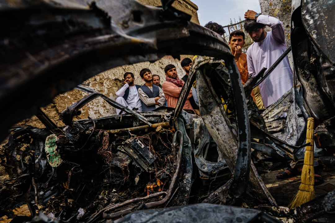 People gather near the burned remains of a vehicle