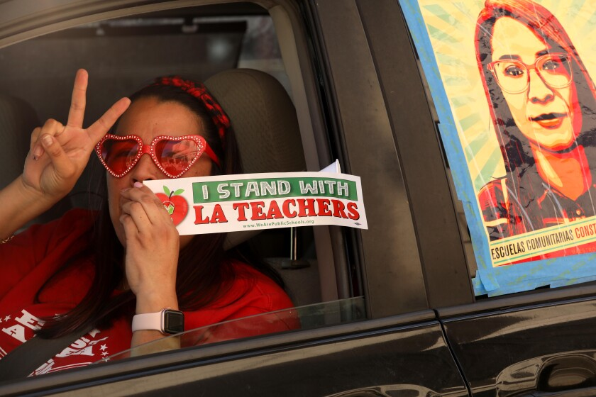 A woman sitting in a car raises two fingers in a V shape and holds a sticker that says I stand with L.A. teachers