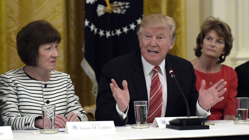 President Donald Trump, flanked by Republican Sens. Susan Collins of Maine (left) and Lisa Murkowski of Alaska at a White House meeting last year. The two moderates, both supporters of abortion rights, may now be key to the confirmation of Trump's next Supreme Court pick.