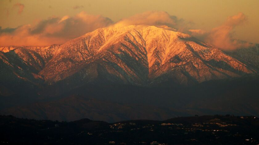 The setting sun casts a golden glow on the snow-covered peaks of Mt. Baldy in 2016. This weekend, snow shut down a main road, stranding scores of people on the mountain.