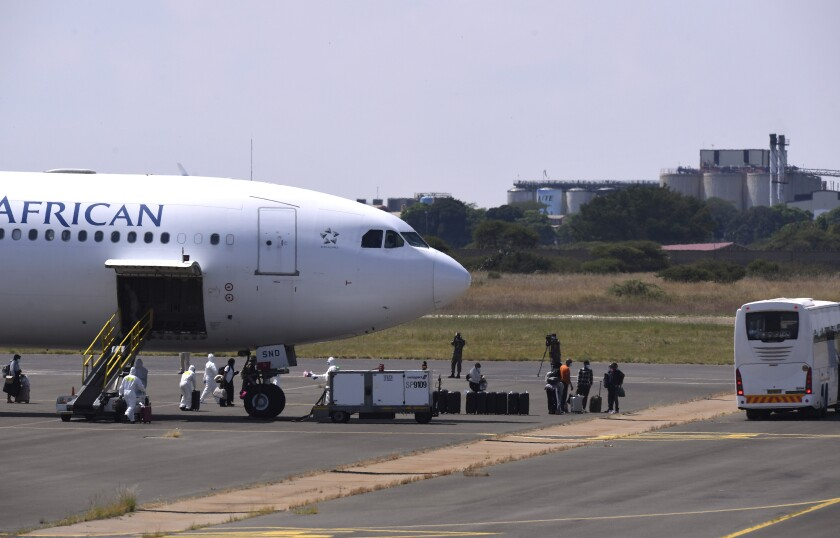 Passengers disembark from a plane on their arrival in Polokwani, South Africa, Saturday, March 14, 2020 after being repatriated from Wuhan, China where they will be kept in quarantine at a nearby resort. For most people the new coronavirus causes only mild or moderate symptoms, such as fever and cough. For some, especially older adults and people with existing health problems, it can cause more severe illness, including pneumonia. (AP Photo)