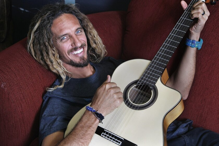 Famed surfer Rob Machado stops for a photo on Friday at The Nest, a student run cafe at Canyon Crest Academy, after appearing at an assembly at school promoting water conservation in San Diego, California.