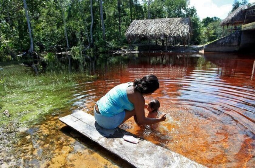A woman bathes her daughter in Puerto Inirida, Colombia. U.S. Rep. Barbara Lee (D-Oakland) fears that climate change will bring about a rise in poverty that will push more women into the sex trade as an alternative to starvation.