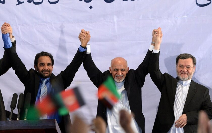 Afghan President-elect Ashraf Ghani Ahmadzai, center, holds hands with his supporters as they gesture to the crowd during a gathering in Kabul on Monday.
