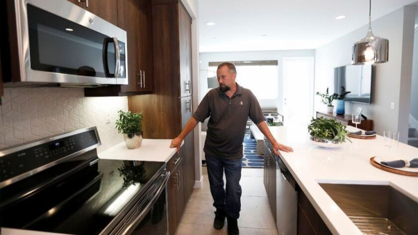 Construction manager Chris Smith shows off an induction cooktop at an all-electric, solar-powered town home development being built by City Ventures in Bellflower, on March 25, 2019.