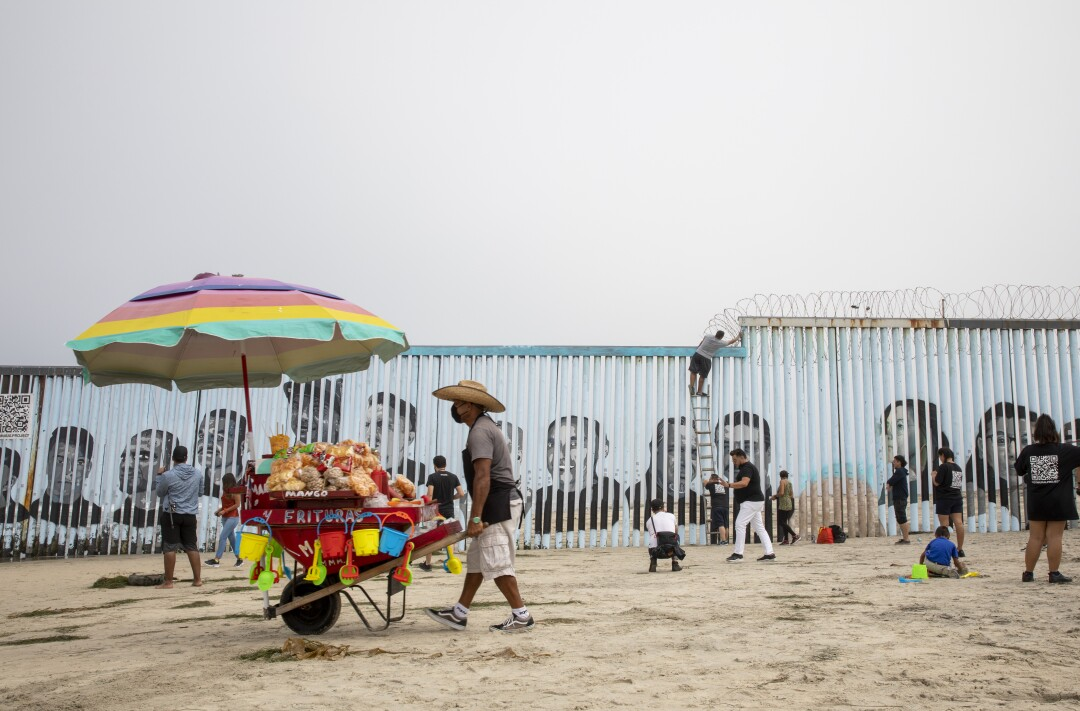 A vendor walks the beach as a new border mural is being finished at Playas de Tijuana