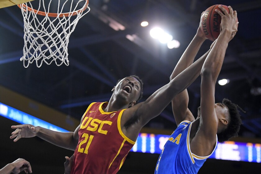 USC forward Onyeka Okongwu, left, and UCLA guard Chris Smith reach for a rebound during the first half on Saturday at Pauley Pavilion.