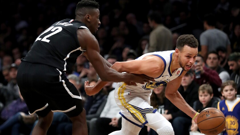 Warriors guard Stephen Curry drives past Nets guard Caris LeVert during the second half Sunday.