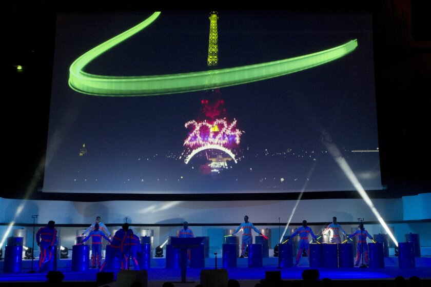 Dancers perform on stage as the Eiffel Tower with 2024 is projected on a giant screen during the official presentation of Paris as candidate for the 2024 Olympic summer games in Paris, France, Wednesday, Feb. 17, 2016. Paris, which hosted the Olympics in 1900 and 1924, is competing against Budapest
