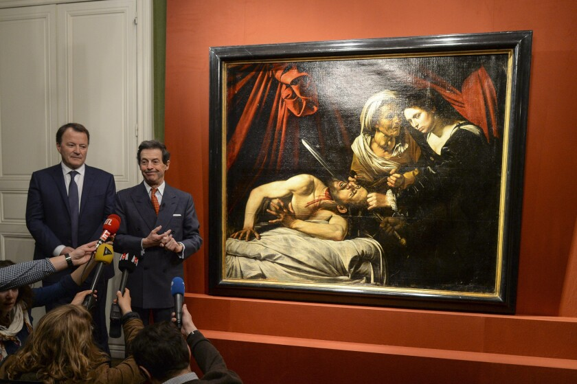 At a Tuesday news conference in Paris, art expert Eric Turquin, right, and auctioneer Marc Labarbe present a work of art that Turquin and others believe was created by Italian Baroque artist Michelangelo Merisi da Caravaggio.