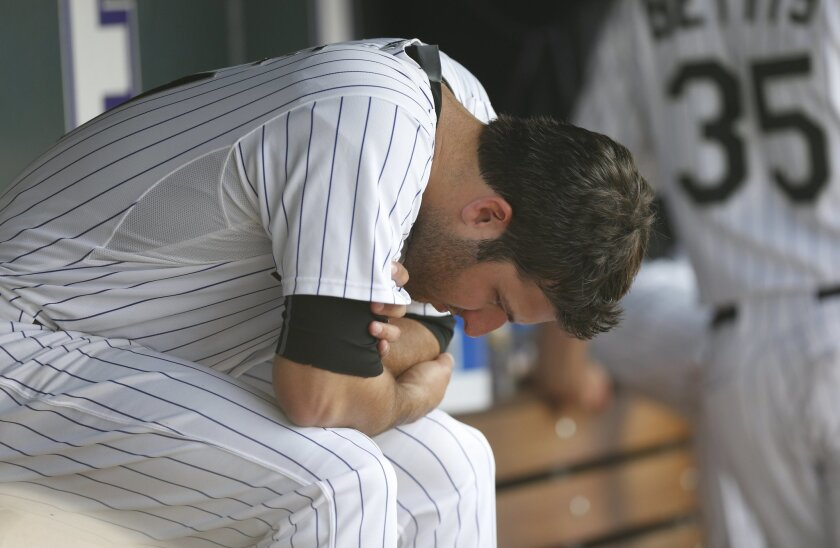 Colorado Rockies starting pitcher David Hale sits in the dugout after retiring the New York Mets in the sixth inning of a baseball game, Sunday, Aug. 23, 2015, in Denver. The Mets won 5-1. (AP Photo/David Zalubowski)