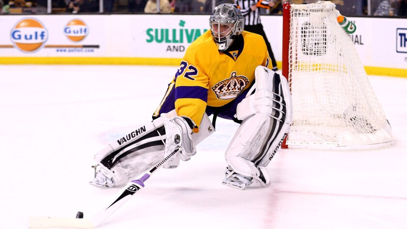 Kings goaltender Jonathan Quick retrieves the puck during a game against the Bruins on Feb. 9.