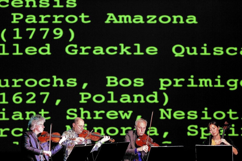 """Kronos Quartet members David Harrington, left, John Sherba, Hank Dutt and Sunny Yang performs """"Landfall"""" with Laurie Anderson (not pictured) at UCLA's Royce Hall."""