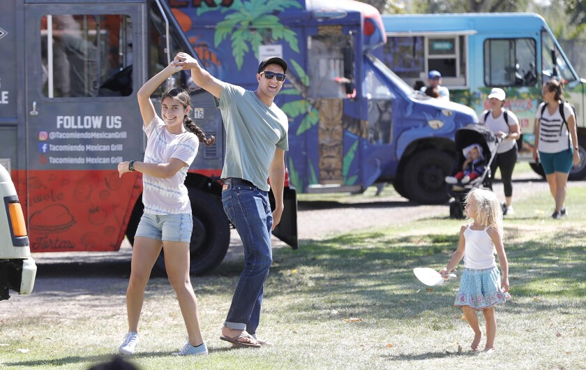 """Gabriel and Isabell Vega dance in front of the food truck during the return of Costa Mesa's """"Concerts in the Park."""""""