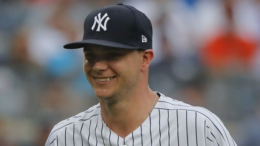New York Yankees starting pitcher Sonny Gray, left, reacts as he leaves the game during the third in