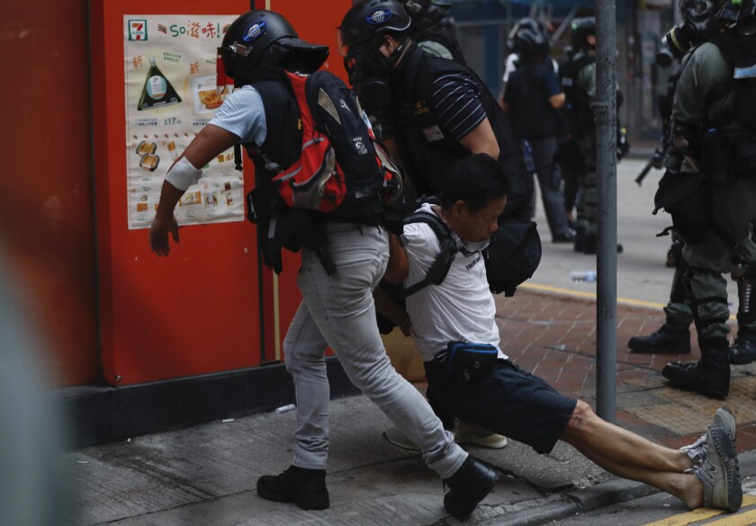 "An injured anti-government protester is attended to by others during a clash with police in Hong Kong, Tuesday, Oct. 1, 2019. Thousands of black-clad protesters marched in central Hong Kong as part of multiple pro-democracy rallies Tuesday urging China's Communist Party to ""return power to the people"" as the party celebrated its 70th year of rule. (AP Photo/Gemunu Amarasinghe )"