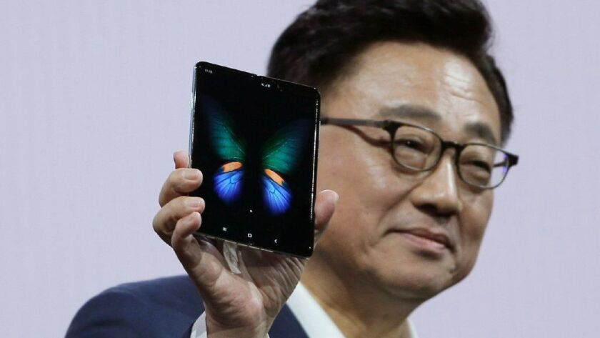 DJ Koh, president and CEO of Samsung's IT and mobile communications division, shows the new Samsung Galaxy Fold smartphone Feb. 20, 2019, in San Francisco.