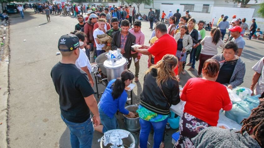 SAN DIEGO, CA November 21st, 2018 | Migrants line up for food served by members of a Tijuana church