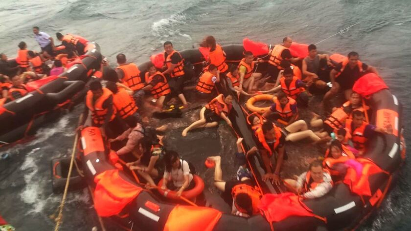 Tourists rescued from a sinking vessel are brought aboard a fishing boat off the coast of Thailand's southern resort island of Phuket on July 6.