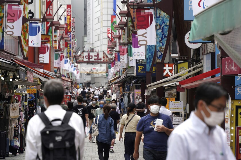 Masked pedestrians shop in a narrow alley in Tokyo as Olympic banners hang above.