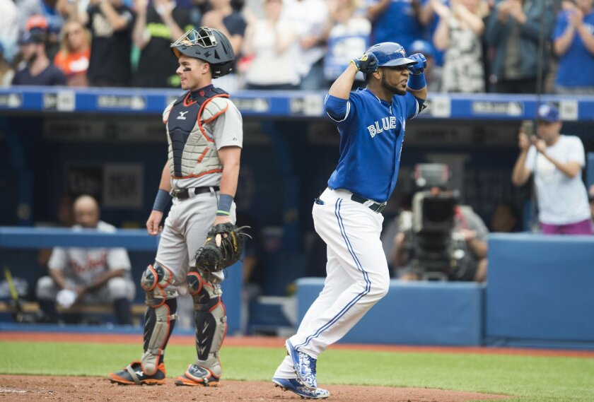 Toronto Blue Jays' Edwin Encarnacion, right, celebrates a three-run home run in front of Detroit Tigers' catcher James McCann during the first inning of a baseball game in Toronto on Saturday, Aug. 29, 2015. (Darren Calabrese/The Canadian Press via AP) MANDATORY CREDIT