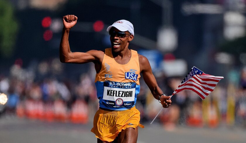 Second-place runner Meb Keflezighi celebrates as he approaches the finish line during the U.S Olympic Marathon Trials.