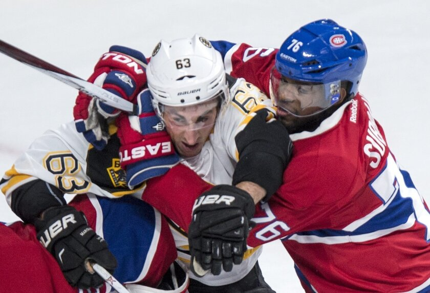 Montreal Canadiens' defender P.K. Subban, (76) holds onto Boston Bruins' Brad Marchand (63) during second period NHL hockey action, in Montreal, on Saturday, Nov. 7, 2015. (Paul Chiasson/The Canadian Press via AP)
