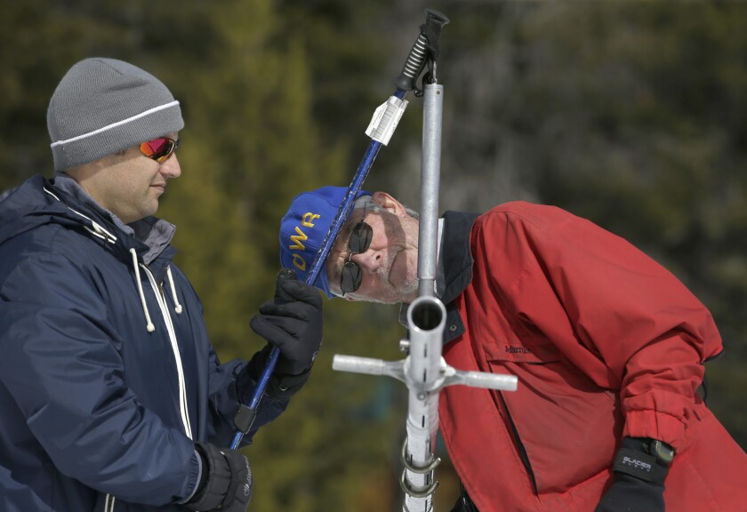 Frank Gehrke, right, chief of the California Cooperative Snow Surveys Program for the Department of Water Resources, checks the weight of the snowpack on a scale held by Brian Brown of the Legislative Analysts office during a manual snow survey Tuesday at Phillips Station near Echo Summit, south of Lake Tahoe.