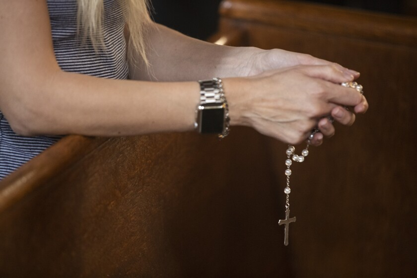 A parishioner holds a rosary