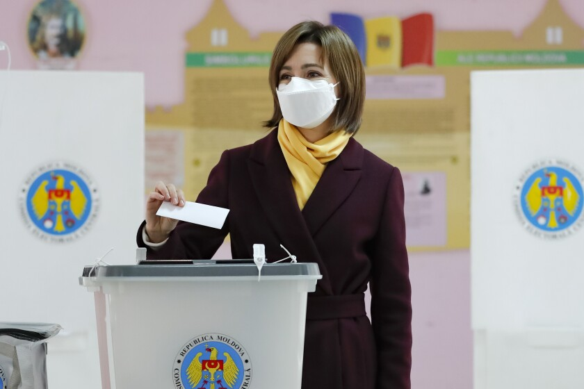 Former prime minister Maia Sandu prepares to cast her vote in the country's presidential election runoff in Chisinau, Moldova, Sunday, Nov. 15, 2020. Moldovans returned to the polls Sunday for the second round of voting in the country's presidential election, facing a choice between the staunchly pro-Russian incumbent Igor Dodon, and his popular pro-Western challenger, former prime minister Maia Sandu. (AP Photo/Roveliu Buga)