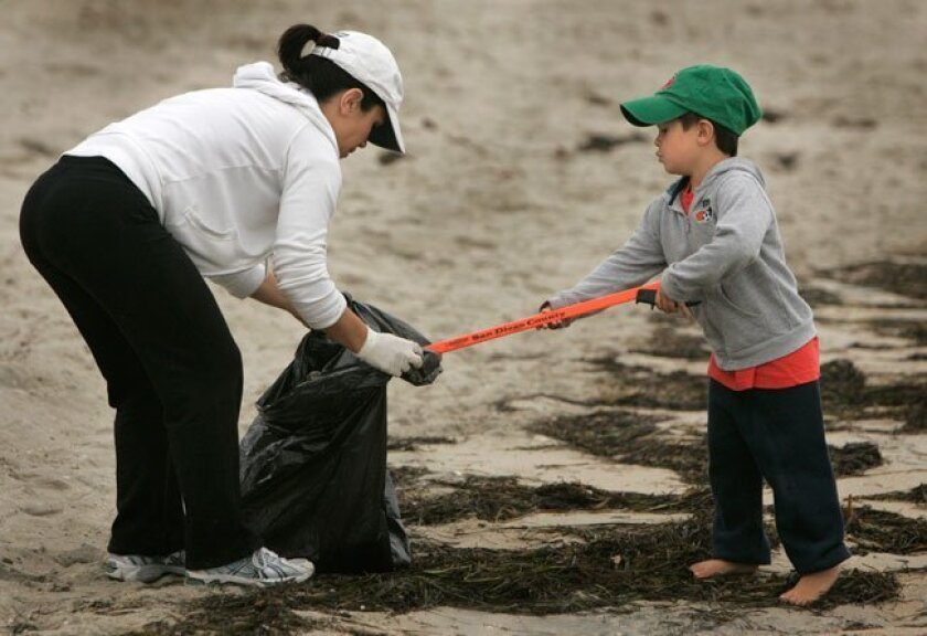 Maria Leahy of Pacific Beach, holds a bag open, as her son, four-year-old Patrick Leahy, places trash in it while helping with the beach cleanup at Sail Bay, early July 5, 2010.
