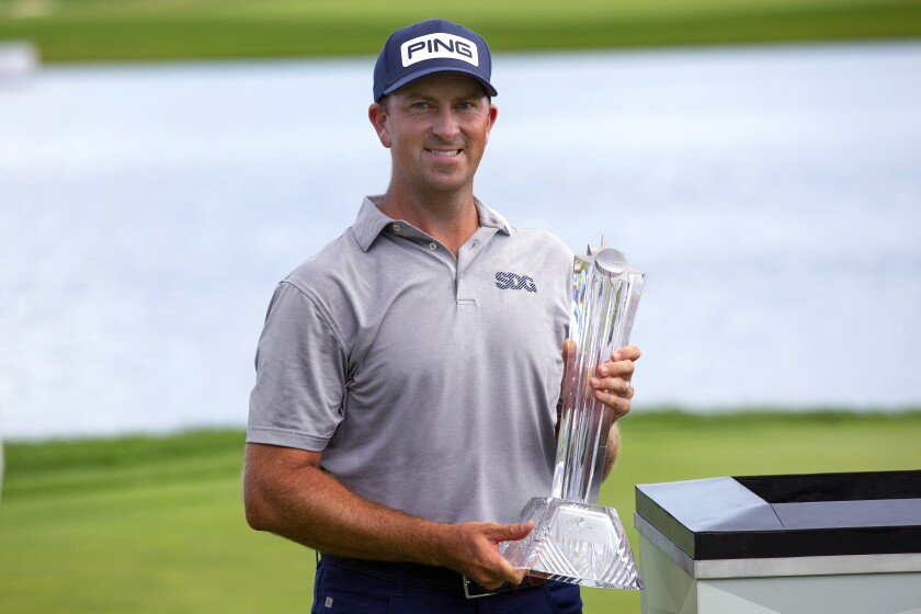 Michael Thompson holds the trophy after winning the 3M Open golf tournament in Blaine, Minn.