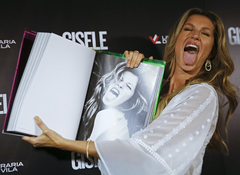 Brazilian model Gisele Bundchen imitates her own gesture as she shows a page of her book, titled Gisele Bundchen, about her 20-year modeling career, before signing autographs in Sao Paulo, Brazil, Friday, Nov. 6, 2015. (AP Photo/Andre Penner)