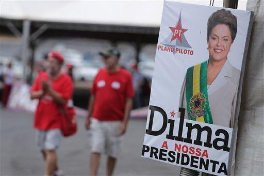 Gente pasa frente a una foto oficial de la presidenta brasileña suspendida Dilma Rousseff en Brasilia, 28 de agosto de 2016. Dilma enfrenta al Senado el lunes 29 de agosto de 2016, al entrar el juicio político en sus atepas finales.