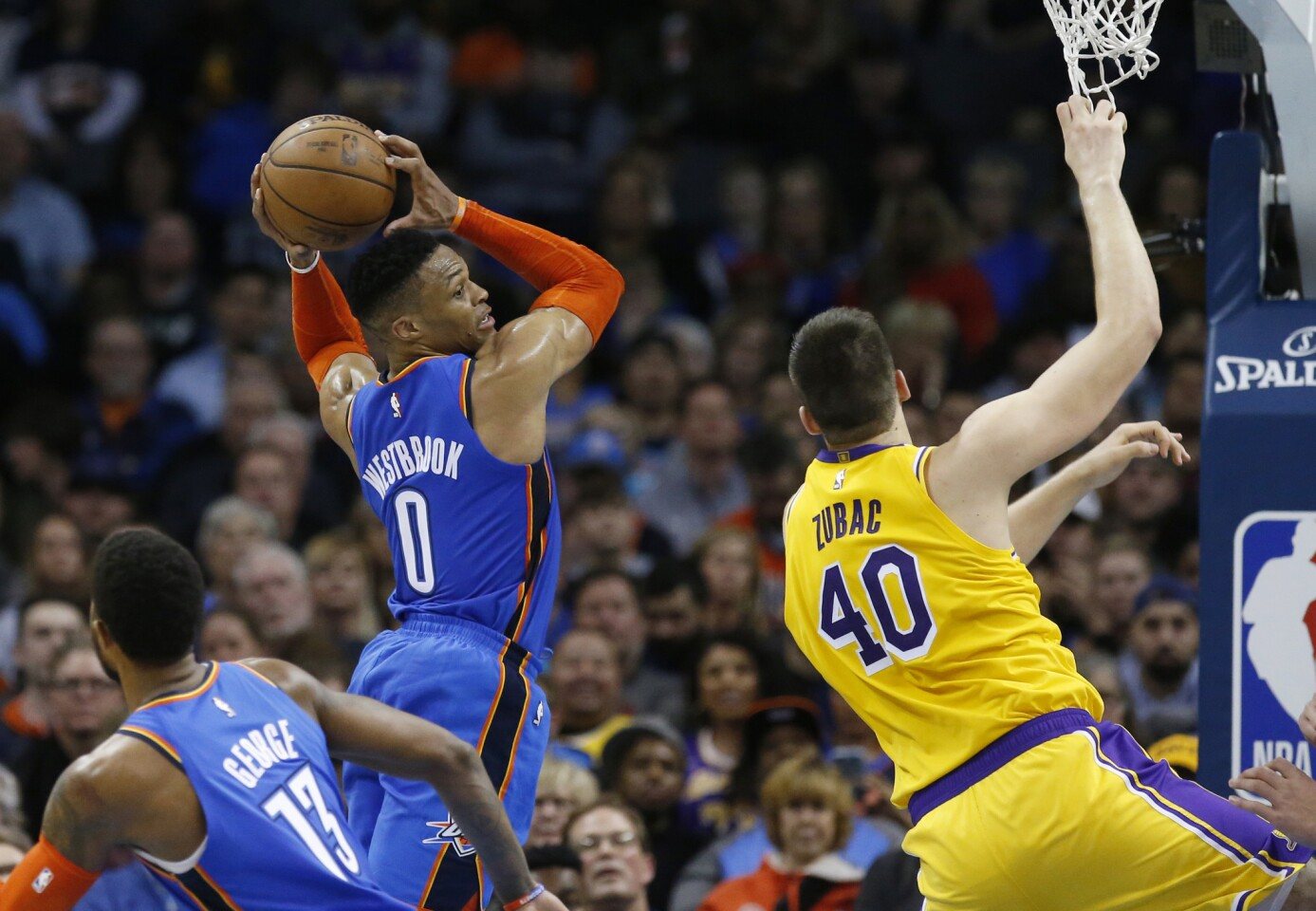 Oklahoma City Thunder guard Russell Westbrook (0) grabs a rebound between teammate Paul George (13) and Los Angeles Lakers center Ivica Zubac (40) during an NBA basketball game between the Los Angeles Lakers and the Oklahoma City Thunder in Oklahoma City, Thursday, Jan. 17, 2019. (AP Photo/Sue Ogrocki)