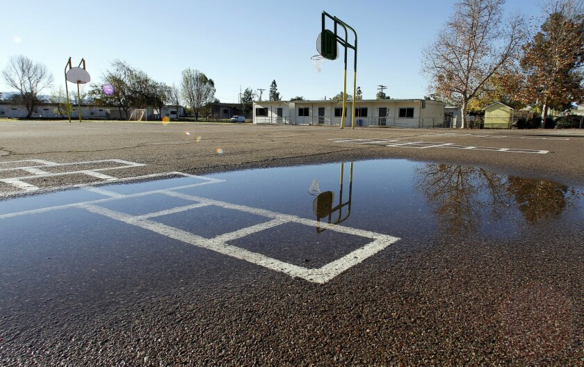 Water puddles in some of the low spots of one of playgrounds at Ramona Elementary School.
