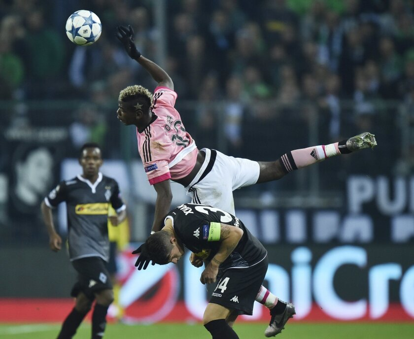 Juventus' Paul Pogba, top, and Moenchengladbach's Granit Xhaka fight for the ball during the Champions League Group D soccer match between Borussia Moenchengladbach and Juventus Turin in Moenchengladbach, western Germany, Tuesday, Nov. 3, 2015. (AP Photo/Martin Meissner)
