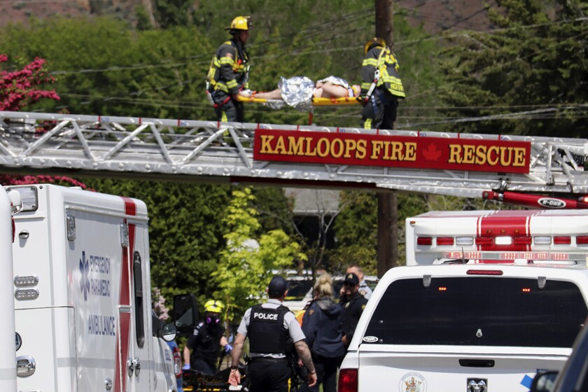 An injured person is carried across a firetruck ladder after being rescued from a rooftop following the crash of an aerobatic jet in Kamloops, Canada, on Sunday.