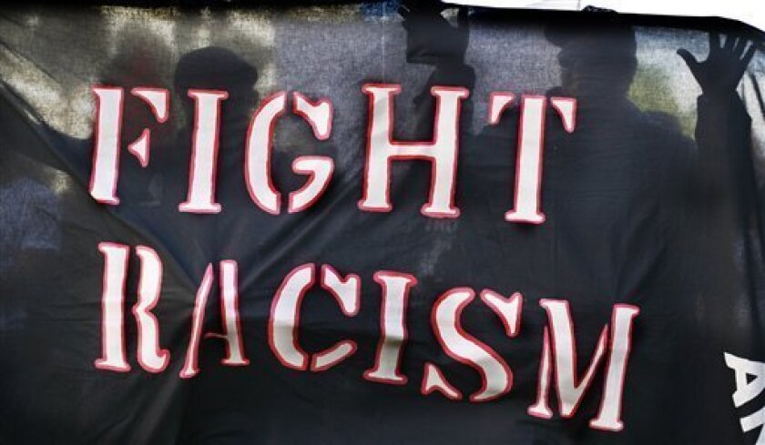 Protestors carry a banner reading 'fight racism' as they take part in an anti-racism demonstration in the center of Geneva, Switzerland, Saturday, April 18, 2009. The United Nations is bracing for a major anti-racism conference opening next week at its European headquarters, with concerns rife that