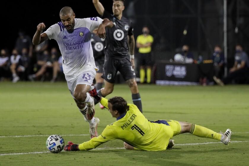 Minnesota United goalkeeper Tyler Miller blocks a shot by Orlando City forward Tesho Akindele during the first half of an MLS soccer match, Thursday, Aug. 6, 2020, in Kissimmee, Fla. (AP Photo/John Raoux)