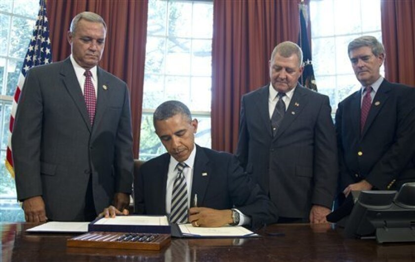 President Barack Obama signs the Honoring America's Veterans and Caring for Camp Lejeune Families Act of 2012, Monday, Aug. 6, 2012, in the Oval Office at the White House in Washington. From left are, Rep. Jeff Miller, R-Fla., Jerry Ensminger, former Master Sergeant, USMC, who served at Camp Lejeune and advocated on behalf of affected veterans and families, and Rep. Brad Miller, D-N.C. (AP Photo/Haraz N. Ghanbari)